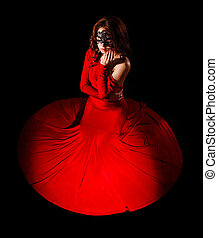 Beautiful young woman sitting in a long red evening dress...
