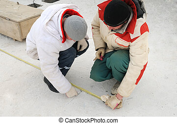 two workers using tape measure