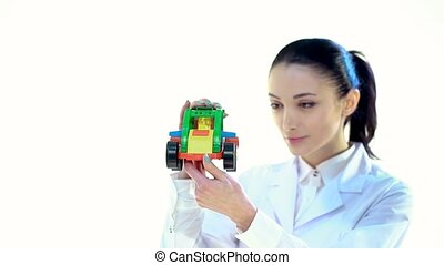 Woman Employee to Look at the Color Plastic Toy Tractor.