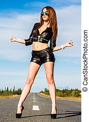 Sexy woman in a black leather clothes on the road - Sexy...
