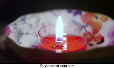 Red decorative candle fire in focus