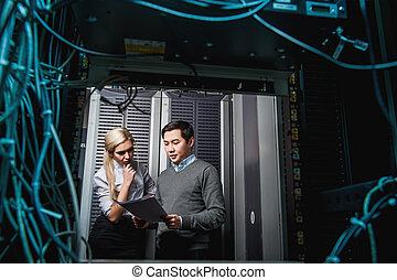 Young engineers businessmen in server room