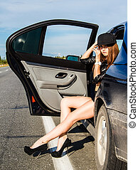 Beautiful young woman sitting at the back seat of a car at...