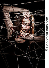 Beautiful young woman behind the interlaced ropes over black...