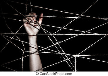 Slim hand behind the interlaced ropes over black background