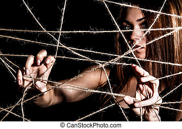 Beautiful young woman behind the net of ropes over black...