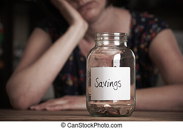 Depressed Woman Looking At Empty Jar Labelled Savings