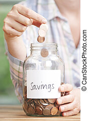 Woman Dropping Coins Into Jar Labelled Savings