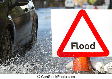 Warning Traffic Sign On Flooded Road With Cars