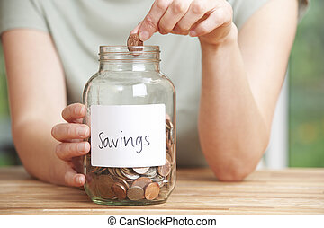 Woman Putting Coin Into Jar Labelled Savings