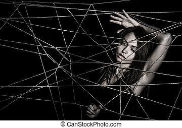 Young woman entangled the net of ropes over black background