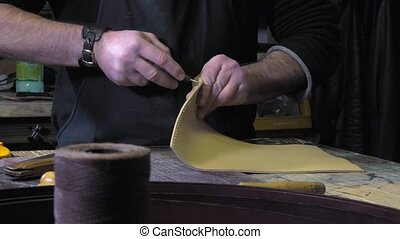 leather goods craftsman at work in - sewing saddle stitch...