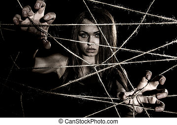 Pale woman snatching the ropes over black background