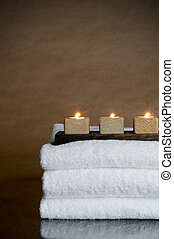 Three candles on three spa towels