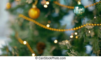 Christmas tree in blur with garlands and balls - Garlands...