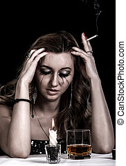 Depressed young woman with a glass of whiskey and a...