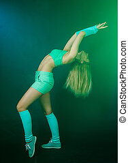 Beautiful young gymnast between blue and green clouds of...