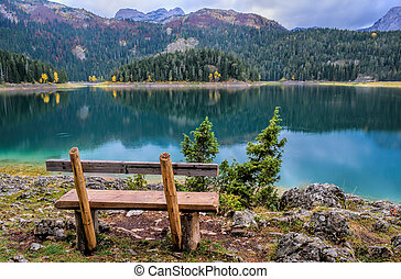 Lake shore - Empty wooden bench on mountain lake shore in...