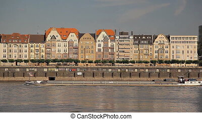 Old buildings near the river in Europe, ships are sailing -...