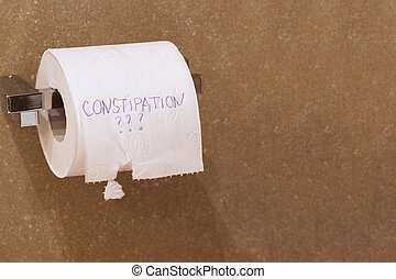 The word constipation written on a tolet paper - The word...