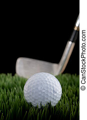 Vertical shallow focus image of a golf ball and club on...