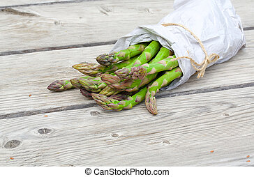 Green asparagus wrapped in a paper - Green asparagus on a...