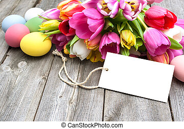 Happy Easter - Easter eggs and tulips with a tag on wooden...
