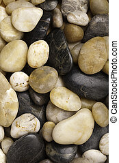 A close-up of numerous types of worn river rock