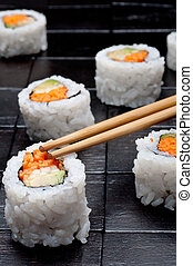 shallow focus vertical close up of sushi with chopsticks on a black wooden background