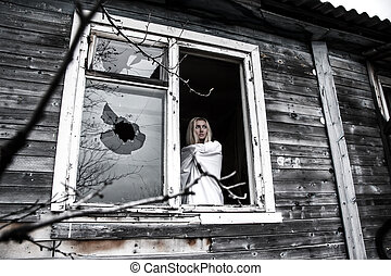 Woman staying near the broken window - Woman in a white...