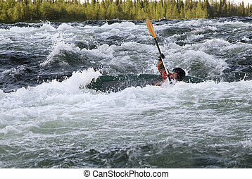Kayaker turning over in whitewater - Kayaker turning over in...