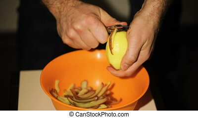 Man peeling potatoes in Kitchen for Prepare food