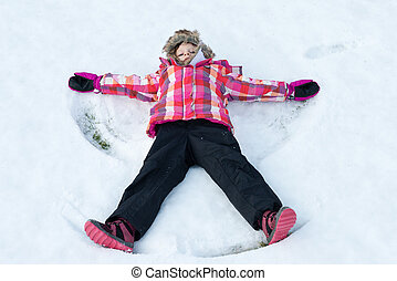 Little girl laying on snow and making angel