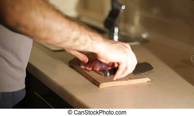 Chef neatly chopping the meat on the cutting board