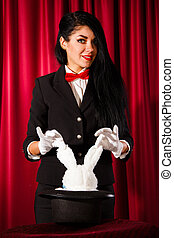 Magician with a rabbit in a hat - Beautiful young magician...