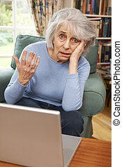 Frustrated Senior Woman Tring To Use Laptop Computer