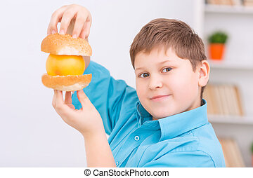 Chubby kid with buns and orange. - Healthy burger. Chubby...