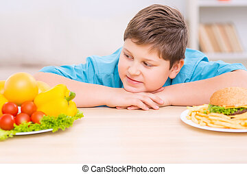 Chubby kid is looking at healthy food plate - Healthy is...