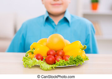 Smiling kid in front of plate filled with veggies - Good...