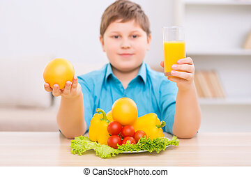 Chubby kid demonstrating healthy products - Organic fooding...