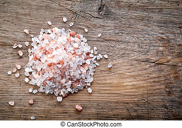 heap of pink himalayan salt on wooden table, top view