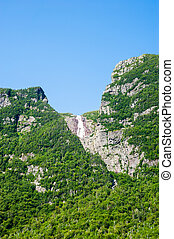 Steep cliffs covered in trees with distant waterfall under...
