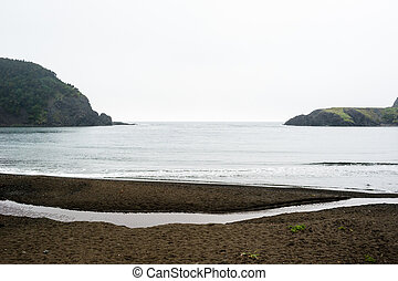 Wet beach in small bay between coastline - Wet beach in...