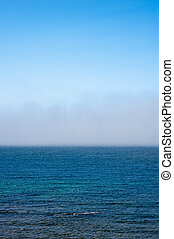 Fog low over wavy water under blue sky - Fog low over...