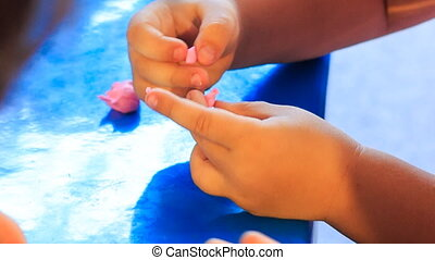 kid's and mother's hands sculpture of plasticine on blue...