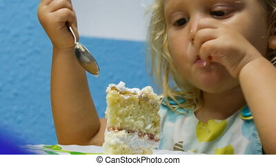 closeup little girl eats piece of birthday cake with tea...