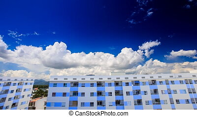 cumulus clouds motion in blue sky over high buildings