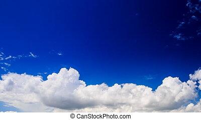 white cumulus clouds motion in blue sky