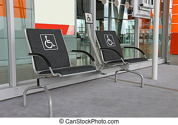 Two seats for people with disabilities in modern airport...