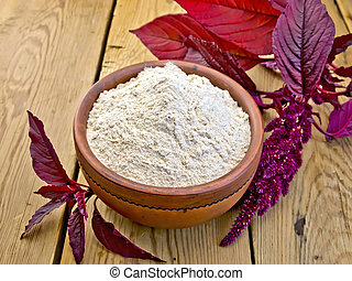 Flour amaranth in clay bowl on board with flower - Amaranth...